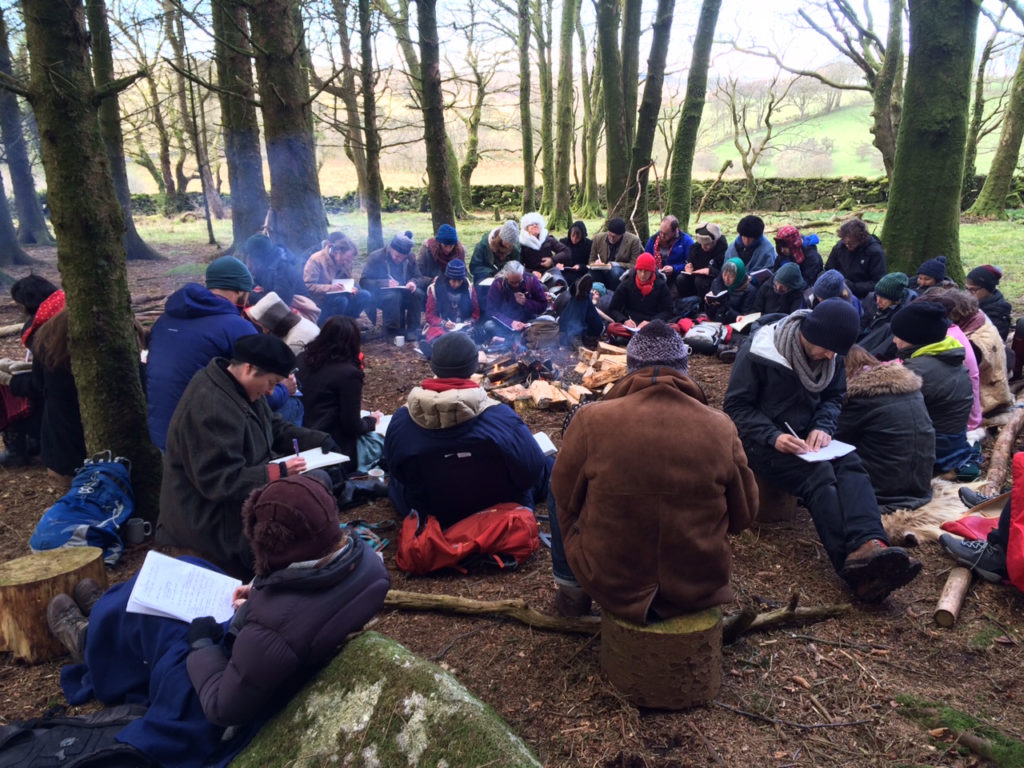 student writing around the fire